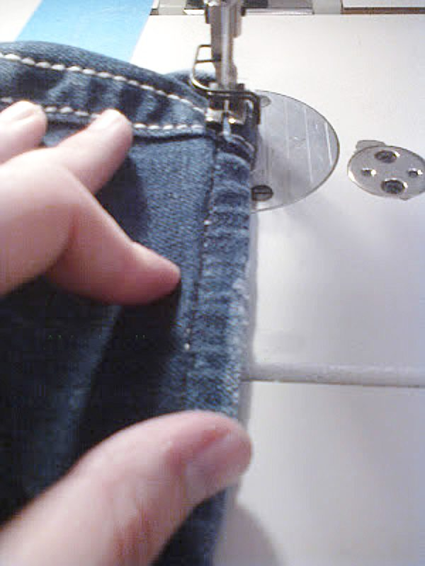 Topstitching being added to hemmed jeans