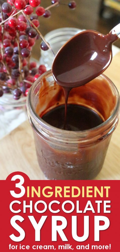 A glass mason jar filled with chocolate syrup with a spoon raising out of the jar to show the thick chocolate syrup running back into the jar.