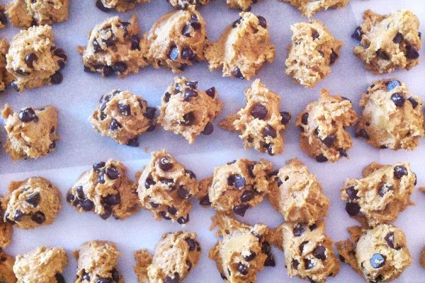 Raw cookie dough portions placed very close together on a parchment lined metal baking sheet.
