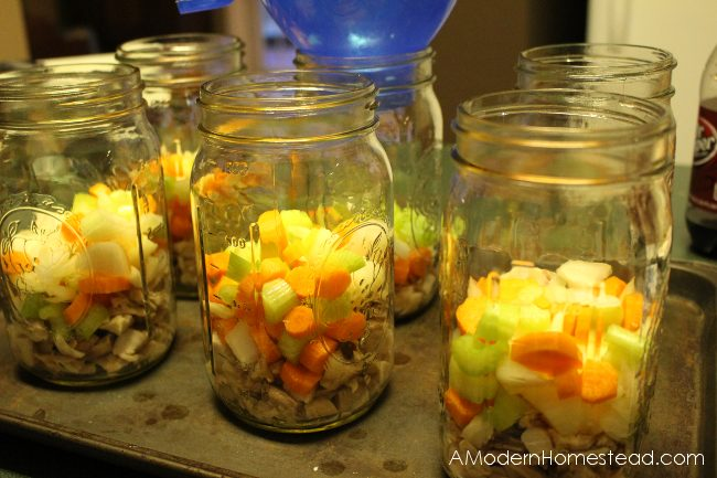 filling canning jars with chicken soup