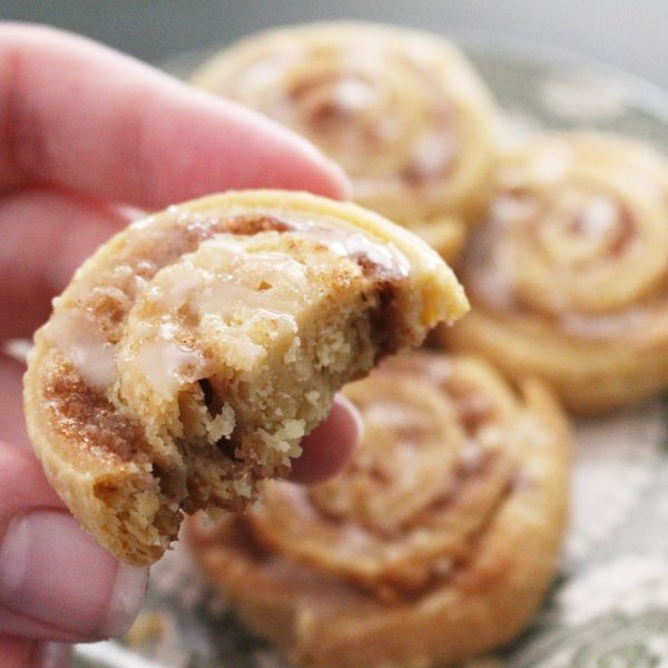 Homemade cinnamon roll cookies with a bite out of one
