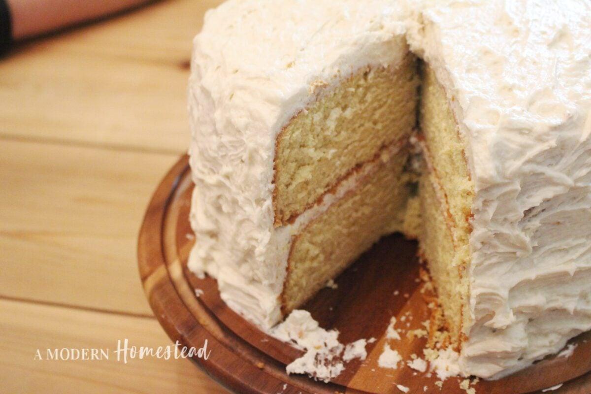 einkorn vanilla birthday cake on wooden stand with buttercream frosting