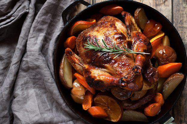 roasted chicken in a baking dish surrounded by vegetables