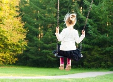 little girl on a swing set facing a spring field