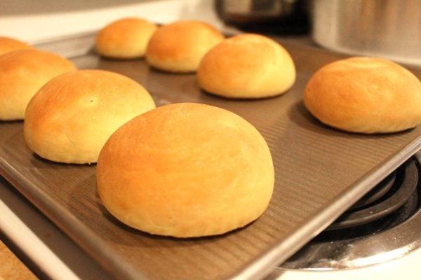 Fresh einkorn hamburger buns on a baking sheet