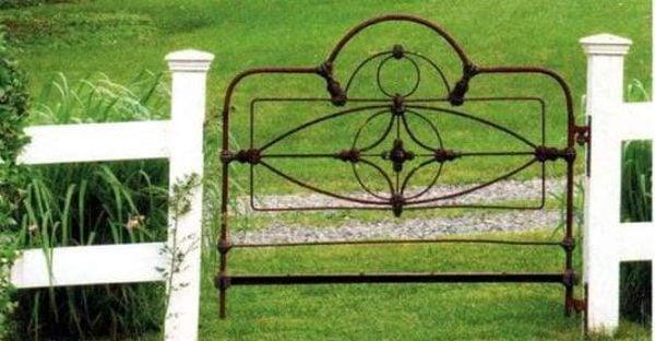 Old bedframe headboard used as a backyard garden gate