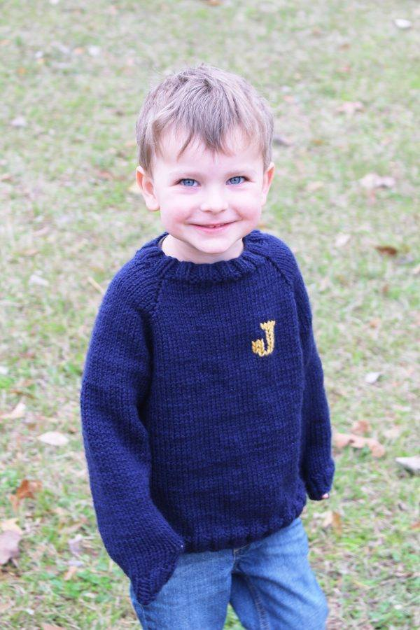 Toddler boy wearing a navy hand-knitted sweater