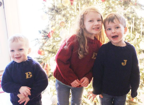 Girl and two boys wearing hand knitted sweaters