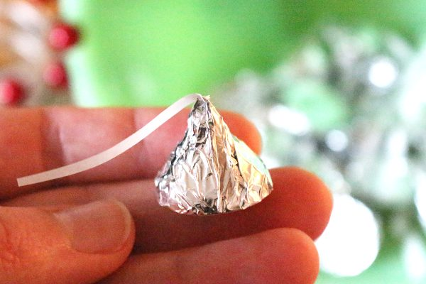 Hand holding silver foil wrapped homemade chocolate kiss