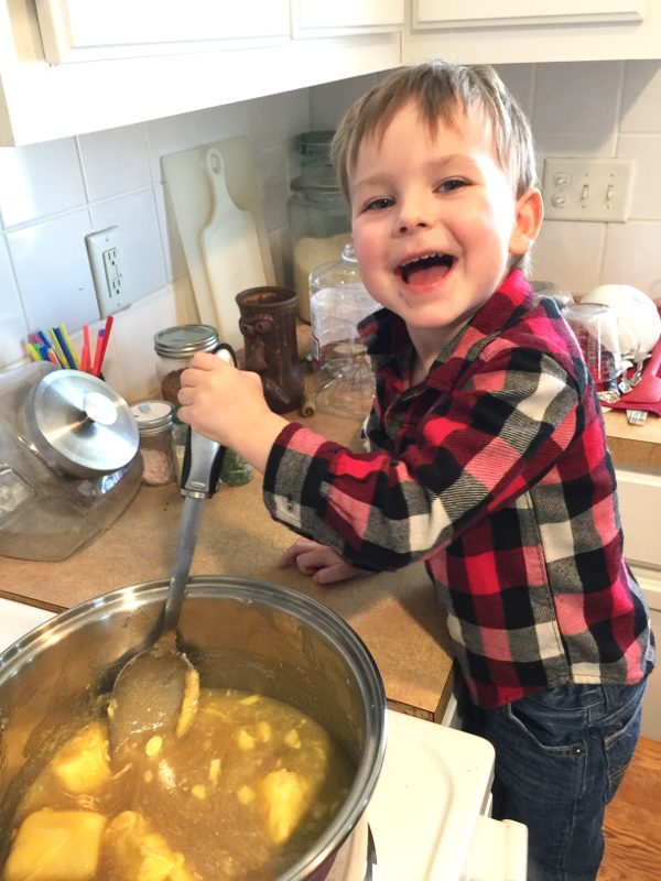 young boy making homemade fudge on the stove