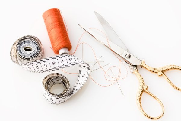tape measure, scissors, and thread on a white background