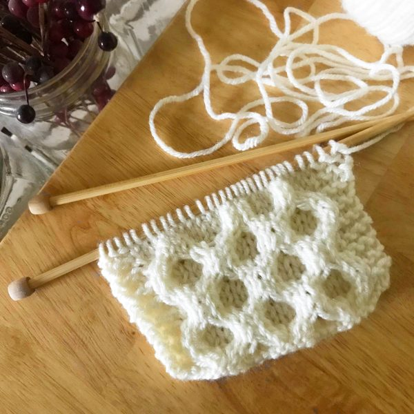 honeycomb cable knit scarf pattern in progress on knitting needles