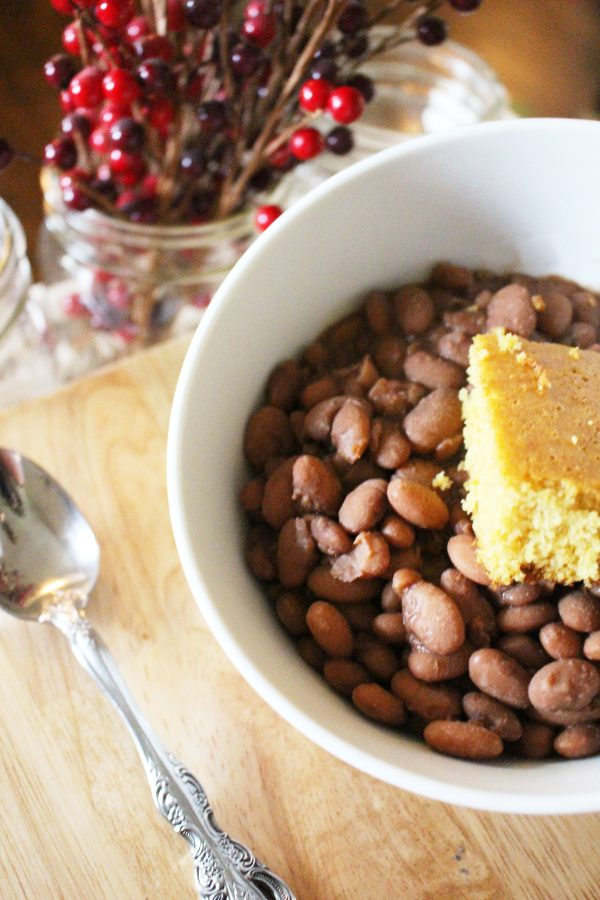 homemade southern pinto beans topped with cornbread in a white bowl