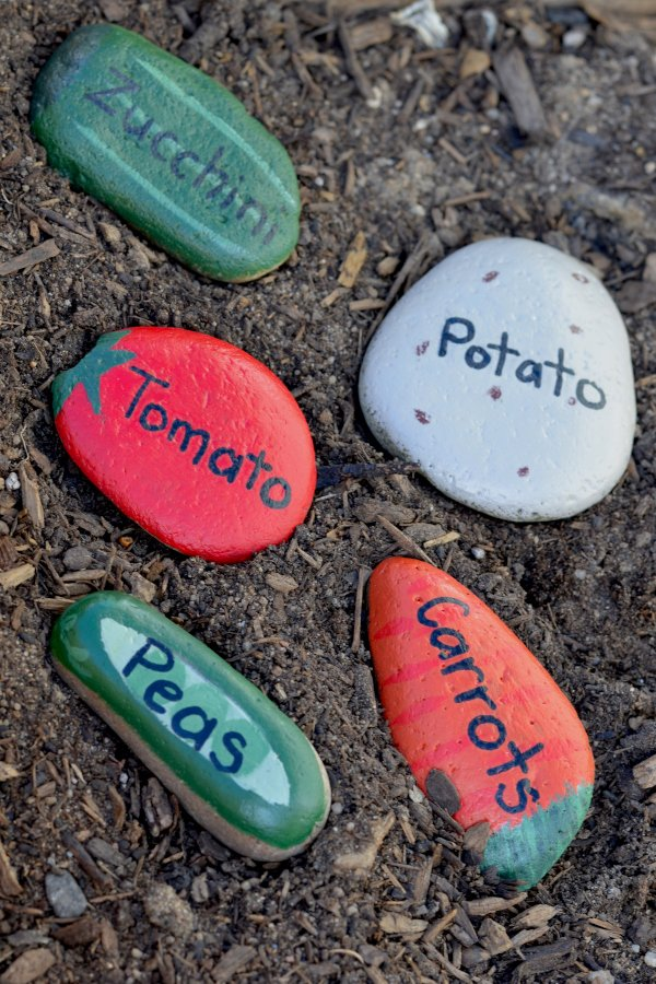 painted rock garden markers sitting in a garden bed