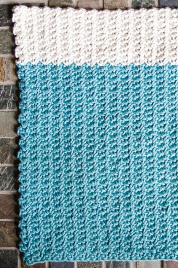 crochet dishtowel on a brick background