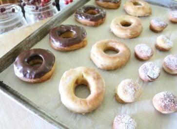 einkorn yeast doughnuts with chocolate glaze or powdered sugar on baking sheet