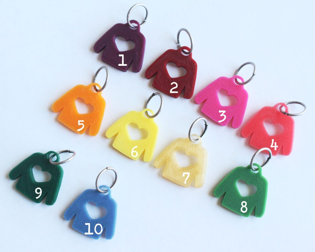 Sweater knitting markers in many colors on white background