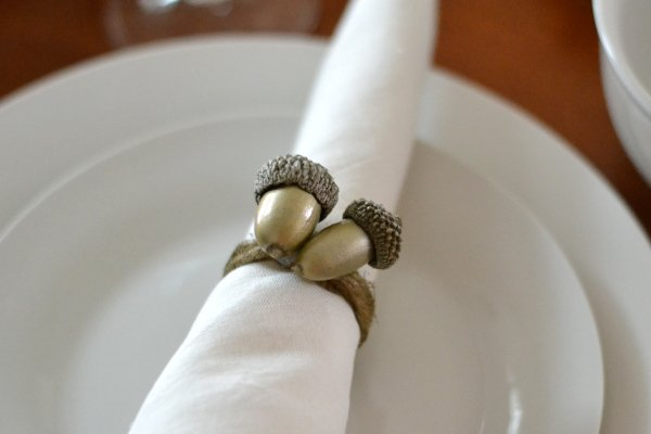 DIY acorn napkin ring sitting on a dinner plate
