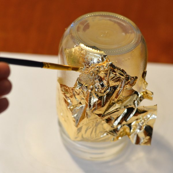 adding gold leaf to a mason jar with a paint brush