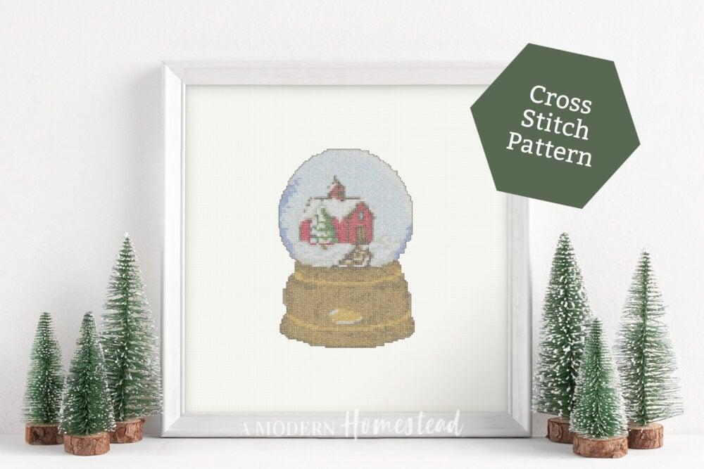 Christmas snow globe cross stitch pattern in a white frame