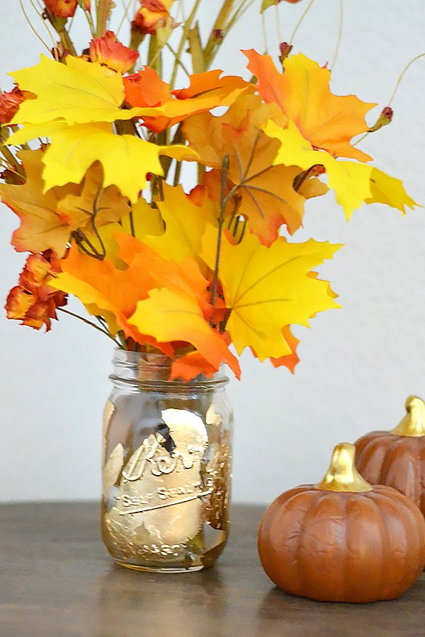 handmade gold leaf mason jar vase sitting on a table