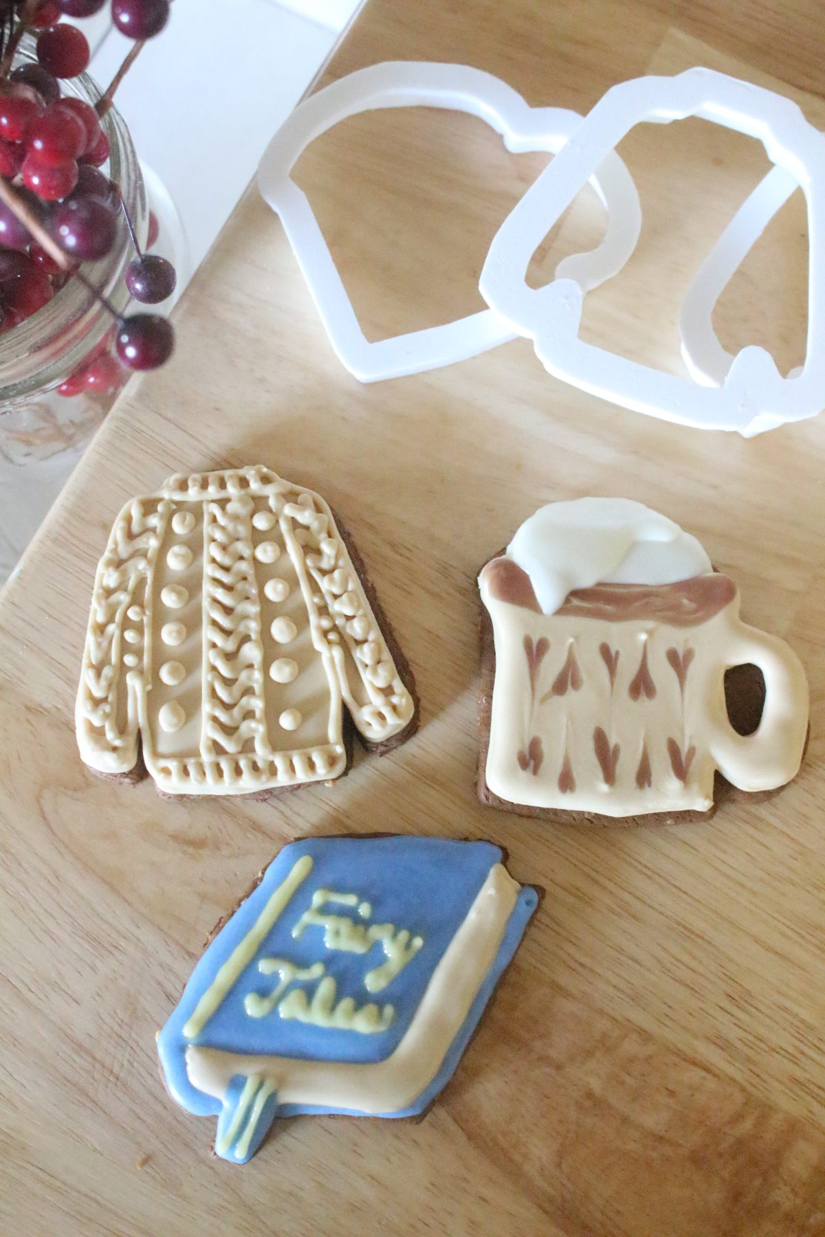 Finished sweater, mug, and book cookies iced with maple powdered sugar royal icing