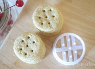 Ritz cracker cookie cutter next to pile of finished homemade Ritz crackers