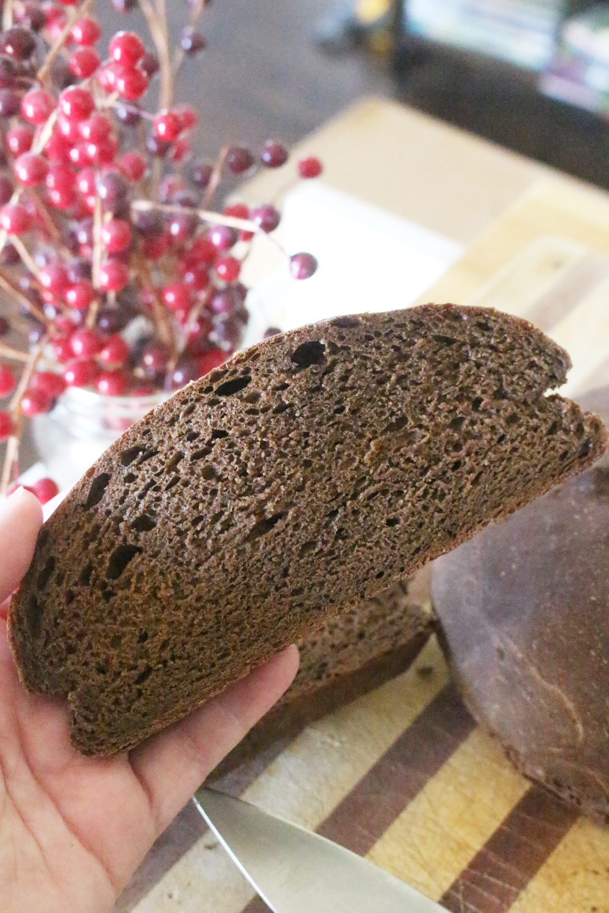 a slice of homemade einkorn brown bread in hand