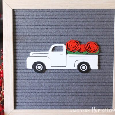 White vintage truck with roses in the bed on gray letter board