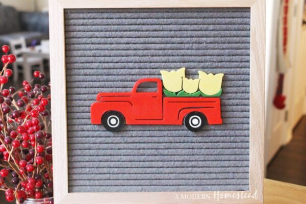 Red vintage truck with tulips in the bed on gray letter board