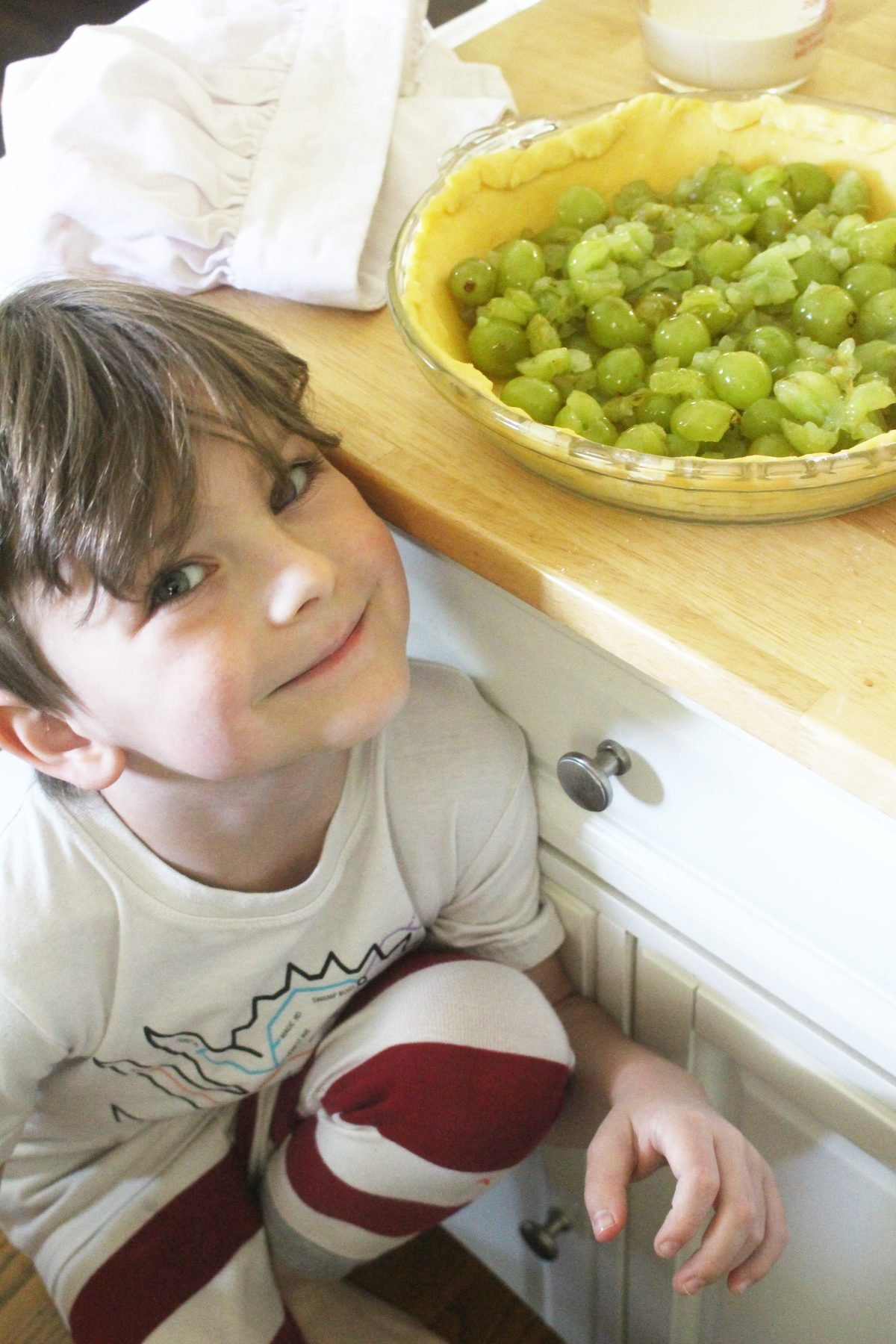 Young boy sitting next to an einkorn pie crust filled with green grapes