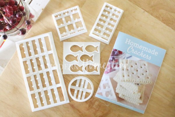 homemade cracker cutters set on wooden counter next to a cracker recipe booklet