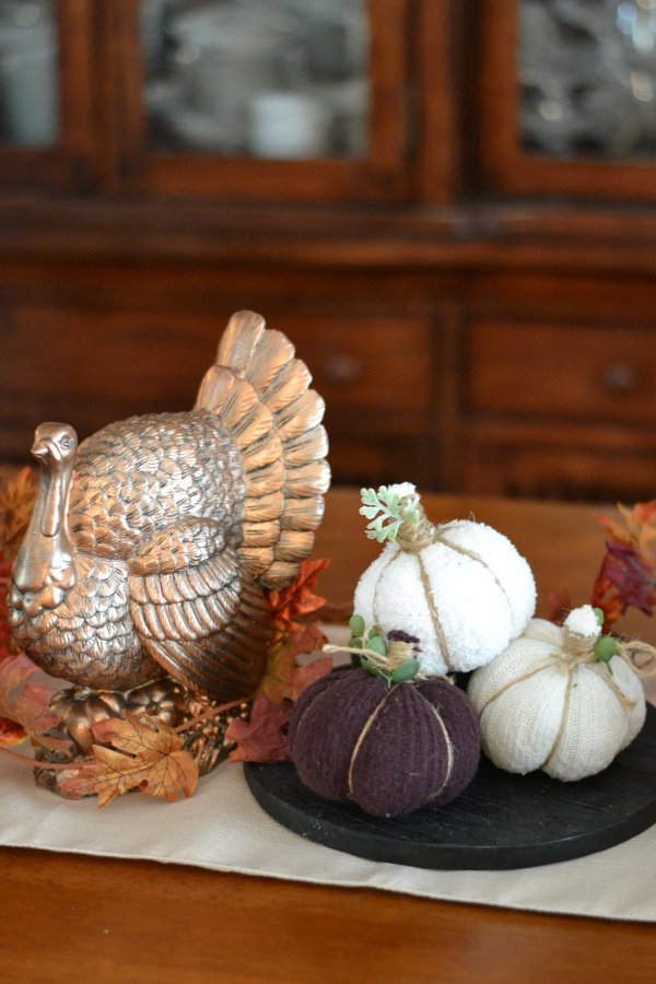 Handmade no-sew fabric pumpkins sitting on a table with fall decorations